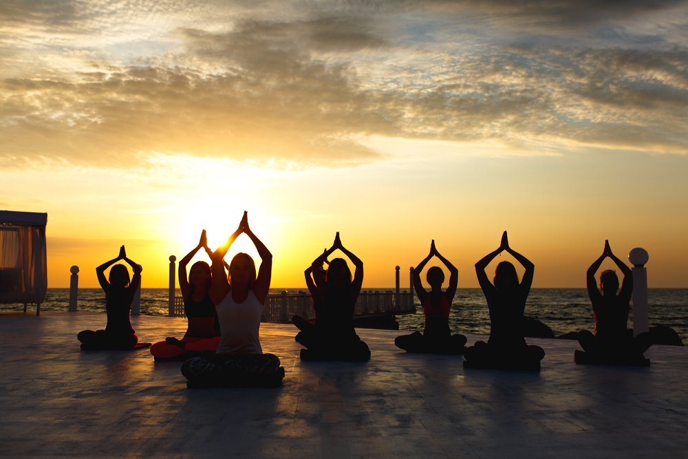 The,Group,Of,Women,Doing,Yoga,At,Sunrise,Near,The